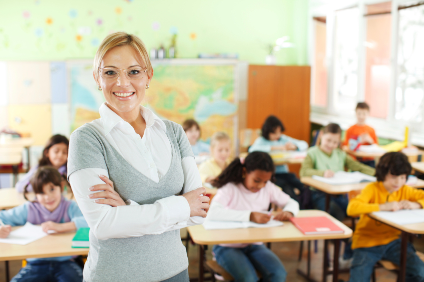 Beautiful smiling female teacher standing and looking at the camera. In the background there is a group of elementary students.   [url=http://www.istockphoto.com/search/lightbox/9786682][img]http://img638.imageshack.us/img638/2697/children5.jpg[/img][/url]